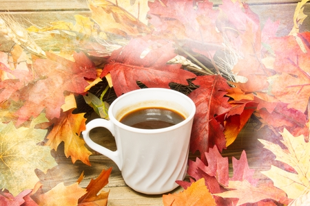 A single hot cup of coffee encircled by leaves in autumn colors on a wooden surface with a texture applied to the fringes of the image. Stock fotó