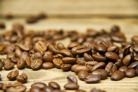 Coffee beans spilled onto a wood table with the focus on the beans near the viewer. Imagens