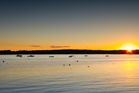 Boats sitting at anchor in Kettle Cove, Main during sunset.