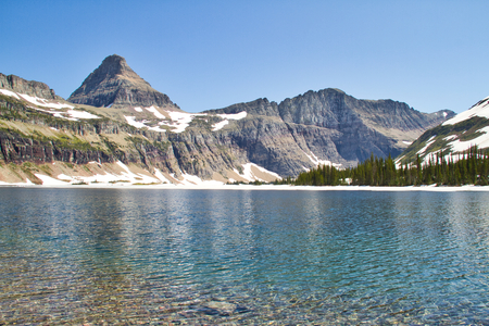 Image from the shore of a clear mountain lake.  This is Hidden Lake in Glacier National Park. 스톡 콘텐츠