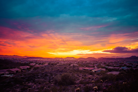 A colorful sunset over a neighborhood in the desert of the American southwest. The sky has warm golden colors on the horizon with cool blue tones in the clouds at the top of the image.