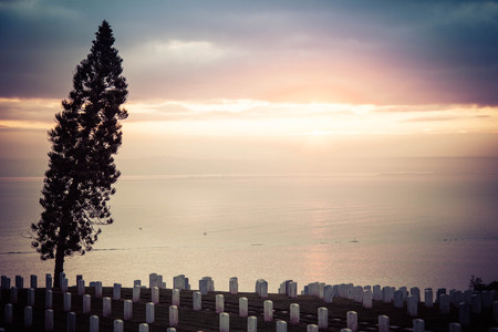 The sun rising over an ocean with a national cemetery in the foreground.