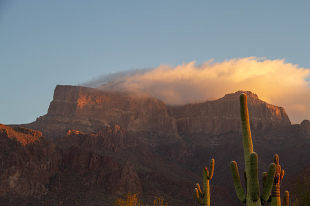 Morning image of the Superstition Mountains of Arizona with a cloud over the peaks reflecting the morning light. 免版税图像
