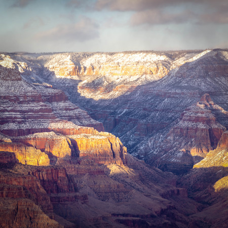 Evening image looking into the Grand Canyon with dramatic evening sunlight casting light and shadows in the canyon.