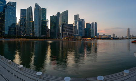 A panoramic image of downtown Singapore during the blue hour with the city lite up and reflecting in Marina bay below.