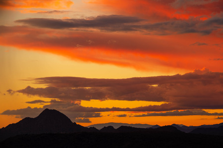Clouds reflecting the light of a colorful sunset with a distant mountain at the bottom of the image.