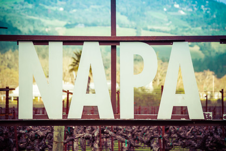 A close-up detail of the Napa Valley sign displaying only the word Napa. A vineyard is in the background alone with a mountain. Stock Photo