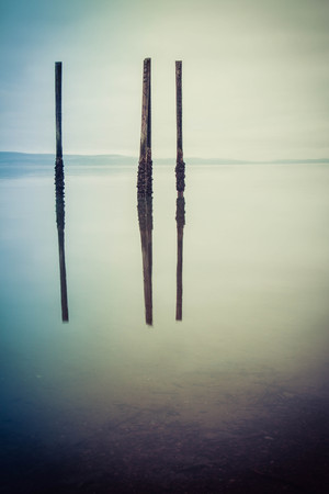 A gloomy image of the calm ocean with wood pilings standing free and reflecting in the water.