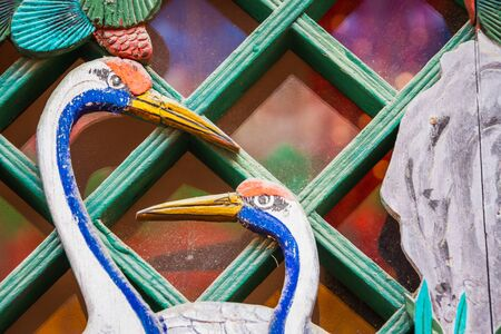 Detail of two wooden storks painted on aged wood over a pane of glass. Banco de Imagens