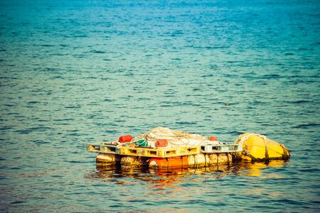 An old fishing raft floating in a harbor with discarded fishing equipment on top of it. 版權商用圖片
