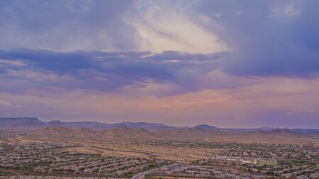 Evening aerial image from a drone of the Sonoran Desert with mountains in the background and a community in the foreground.