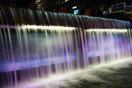 A waterfall flowing at night with purple lights illuminating it.