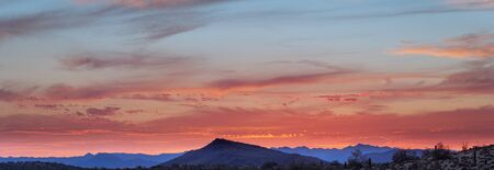 A sunset over a distant mountain in the Sonoran Desert of Arizona panorama