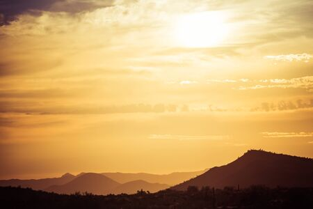 A sunset over a distant mountain in the Sonoran Desert of Arizona