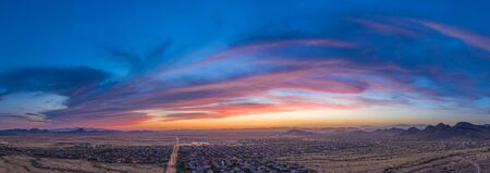Panoramic aerial view of a desert community in Arizona during the golden hour at sunset.