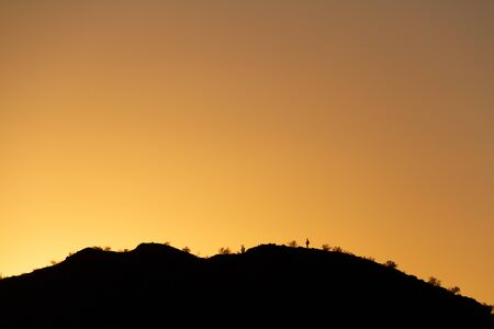 The sun setting behind a mountain in the Sonoran Desert of Arizona, filling the sky with golden light. Фото со стока