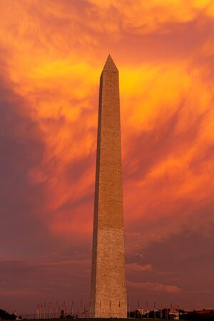 The Washington Monument during sunset with the clouds behind the monument lite in brilliant evening colors.