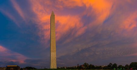 Panorama of the Washington Monument during sunset with the clouds behind the monument lite in brilliant evening colors.