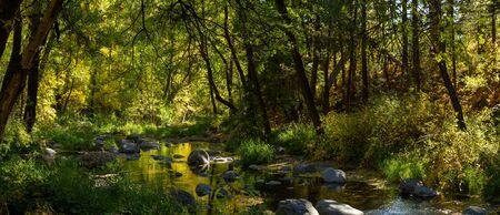 Panorama de los colores de principios del otoño sobre Oak Creek en las afueras de Sedona, Arizona, con agua que fluye sobre y alrededor de las rocas.