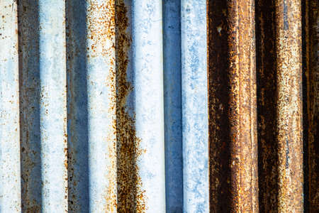 Rusted corrugated sheet metal siding background showing its age and weathering.