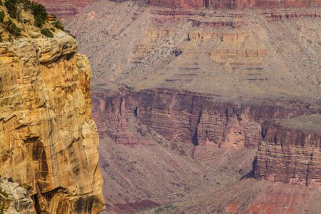 Zoomed in image with a cliff face and the Grand Canyon in the background.