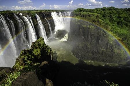 simbabwe: Die Victoria Falls mit Regenbogen in Simbabwe. Lizenzfreie Bilder
