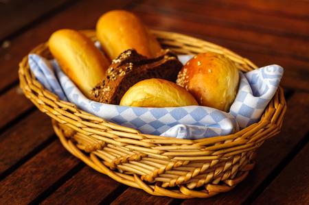 canasta de pan: Varios tipos de pan en la canasta en una mesa.