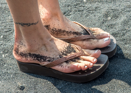 foots: A gril foots on the black sand beach in Maui, Hawaii.
