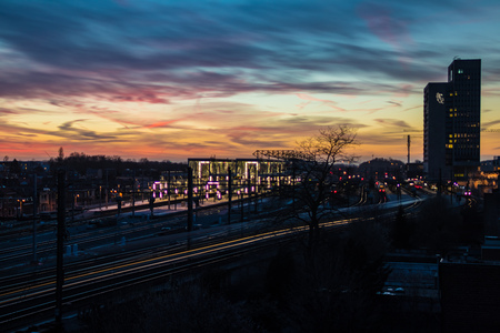 Very colorful and contrasted sky at sunset from above Ghent Sint Pieters, the main train station in Ghent, Belgium. Lights of the train passing by in the foreground low shutter speed.
