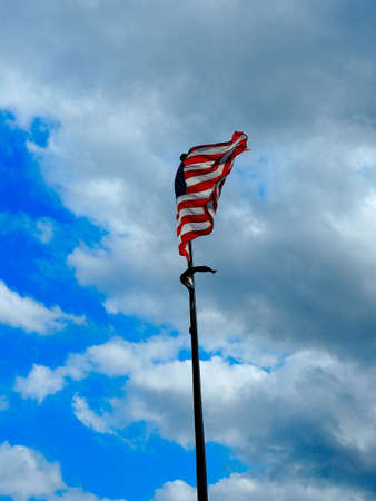 clouded sky: American flag on the blue clouded sky Stock Photo