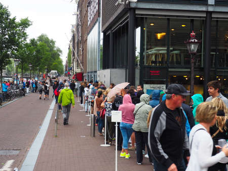 file d attente: Amsterdam, Pays-Bas, Eté 2015. Partie avant d'une ligne logn d'attente pour la célèbre Maison d'Anne Frank Éditoriale