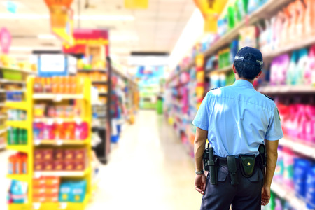 vigilante: Security guard in supermarket blurry