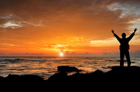 ein Mann mit den Händen auf schöne Silhouette Sonnenuntergang angehoben
