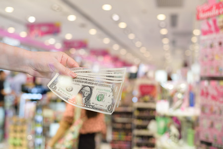 give money: Hand give money dollars in shopping mall