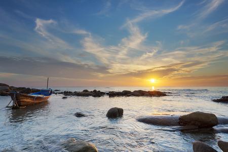 Un petit bateau dans le temps du coucher du soleil