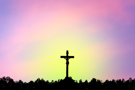 Silhouette the cross over blurred sunset background. Stock Photo