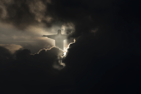 jesus Christ in dark sky with clouds, bright light from heaven, resurrection concept,