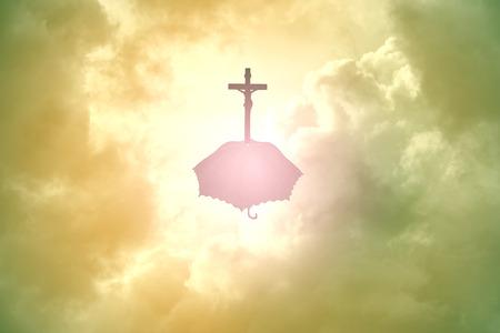イエスとクロスの傘雲の上をシルエットします。 写真素材