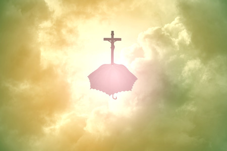 Silhouette Jesus and the cross umbrella above clouds Stock Photo