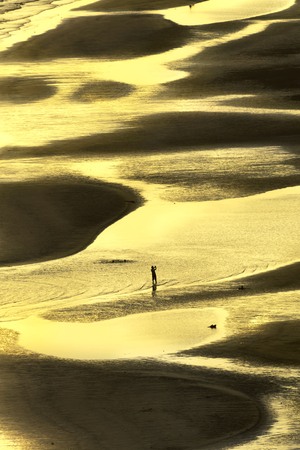 silhouette golden light people walk on tropical Chao Laow beach in Chanthaburi