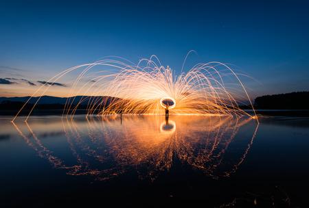 Fire steel wool in the lake at sunrise . Stok Fotoğraf