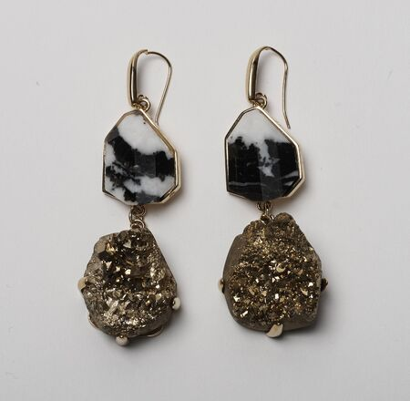 Elegant loop earrings with black marble and golden stone at bottom with white background, Elegant loop earrings with black marble and golden stone at bottom with white background Foto de archivo