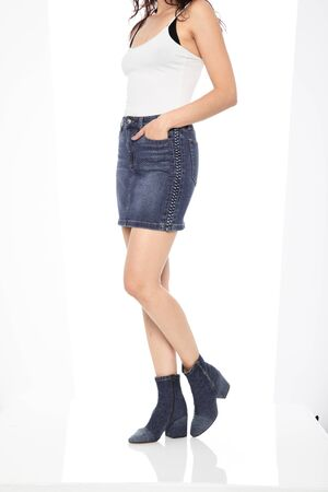 Blue denim ripped shorts for women's paired with white tank top and black footwear with white background Zdjęcie Seryjne - 134744527