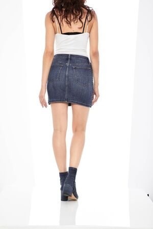 Blue denim ripped shorts for women's paired with white tank top and black footwear with white background Zdjęcie Seryjne - 134744533