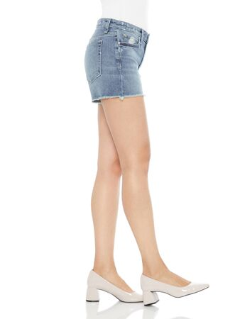 Blue and white denim ripped shorts for women's paired with white tank top and black footwear with white background Stock fotó