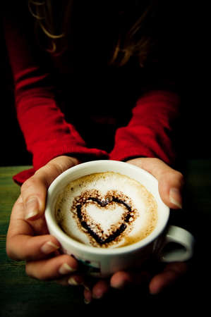offered: Heart shape in a cup of coffee offered by young girl Stock Photo
