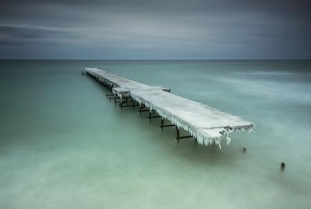 Winter landschap met oude kapotte brug onder de stormachtige zee