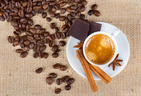 Coffee cup, cinnamon, chocolate and coffee beans on a burlap background photo