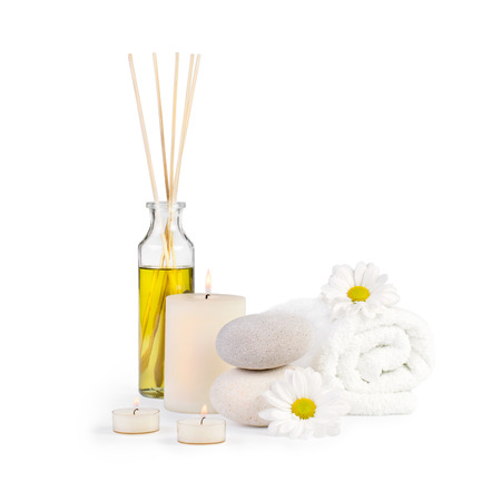 Spa decoration with stones, daisies, candles and a bottle with massage oil on a white background photo