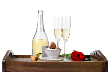 Romantic decoration with rose, champagne and chocolates on a wooden tray isolated on white  photo